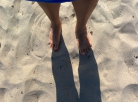 Brown skinned legs standing in the sand