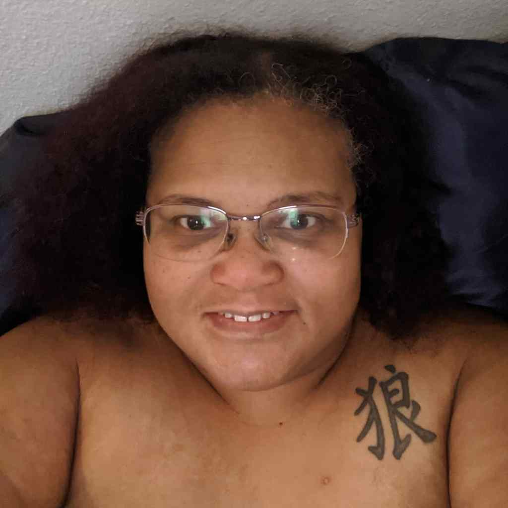 Brown skin woman with dark brown hair facing the camera with a small amil